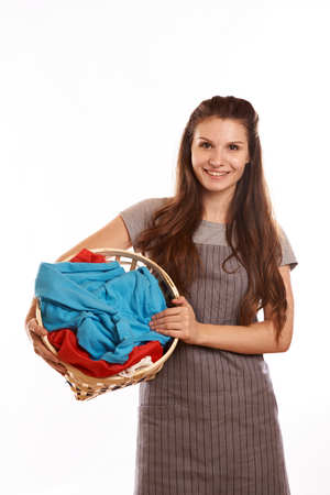 woman doing a housework holding laundry isolated over white background.