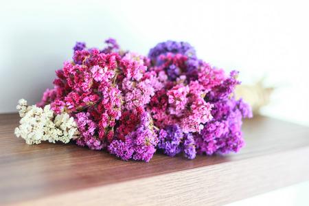 dried flower arrangement: colourful statice flower bouquet on wooden floor
