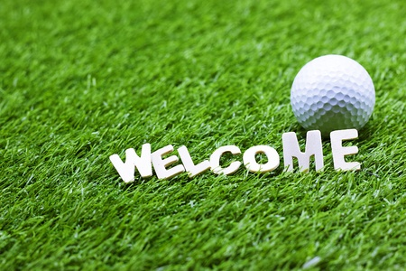 Welcome word with golf ball is on green grass 写真素材