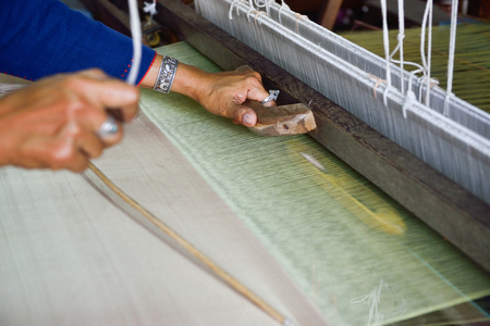handloom: Thai woman hand weaving silk being used to make cloth