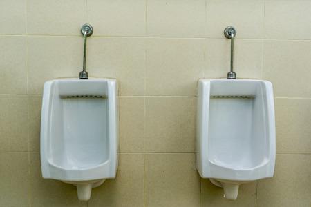 public restroom: Automatic urinals in mens public restroom toilet.