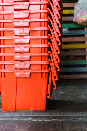 red plastic storage containers stacked on wooden floor