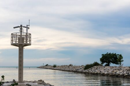 seawall: lighthouse and cement seawall in evening landscape view