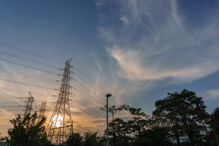 circulate: high voltage electricity post with sunset background, silhouette