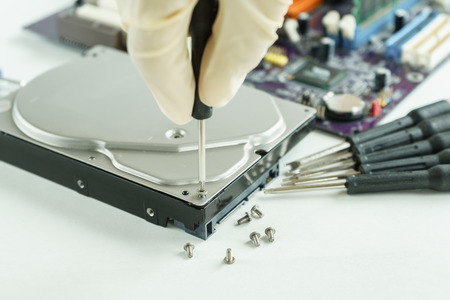 data recovery: hand holding screwdriver to open hard disk drive for recovery information, data storage