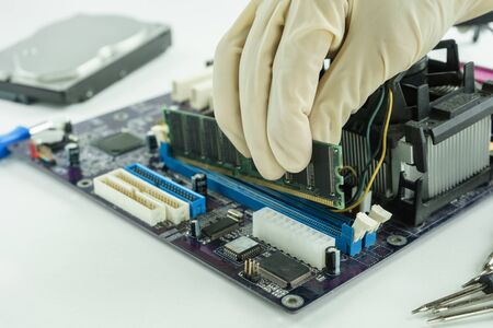 computer services: hand holding random access memory to install in socket, installing RAM on PC main board