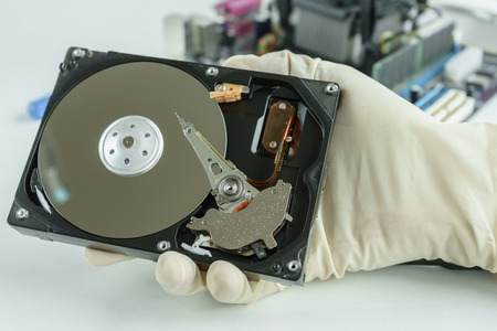 data recovery: opened hard disk drive in hand ready to repair and recovery data storage