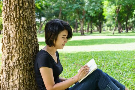 reading and writing: Asian young girl sit to writing letter under the tree in green park