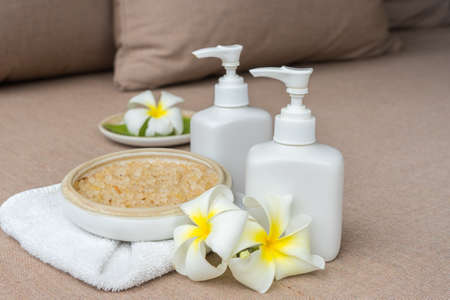herbs boxes: White lotion bottles for spa treatment on spa bed
