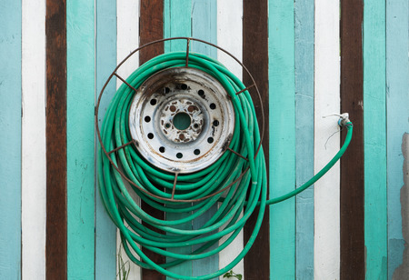 water hose: Water hose hang on the wooden wall outdoor in garden