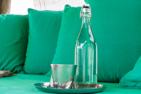 Glass Water bottle prepare for guest with colorful pillow in background