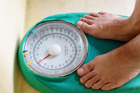 weigh machine: Mans feet standing on weighing machine, weighing scale