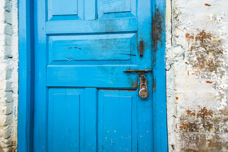 private access: Wood door in blue color is locked with padlock, texture and background