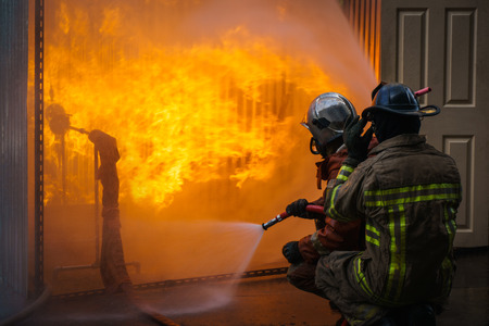 la formación y la lucha contra un bombero llamas del fuego ardiente Foto de archivo