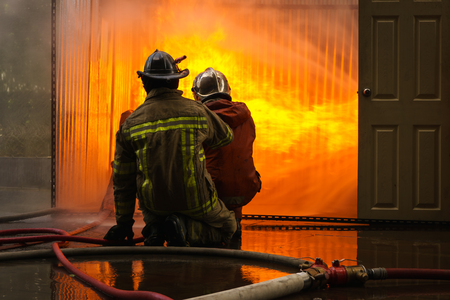 fireman with hose: Firemen fighting a flames of burning fire, fireman training