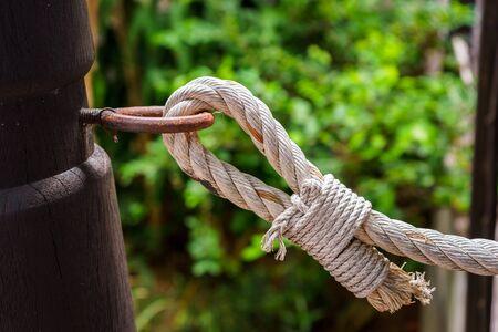 nudo: El enganche de perfiles es una cuerda de nudo atado a un poste de madera Foto de archivo