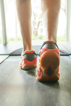 health care facilities: Exercise running for healthy, Closeup Mans legs on treadmill in fitness gym Stock Photo