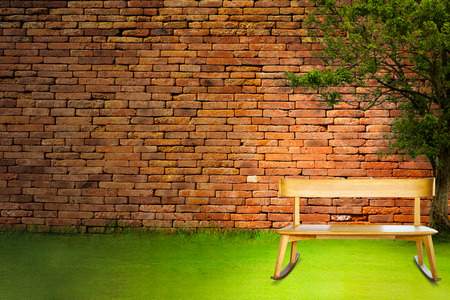 baseboard: Seat and Relax with bench on grass near brick wall, Bench for text space background