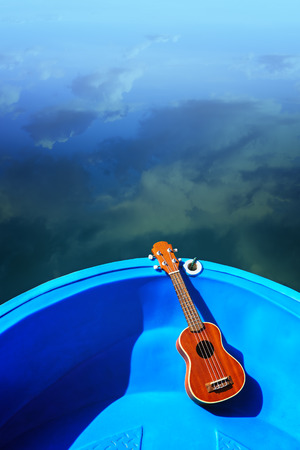 Ukulele lay on blue boat floating on water, relax with instrumental Ukulele Stock Photo