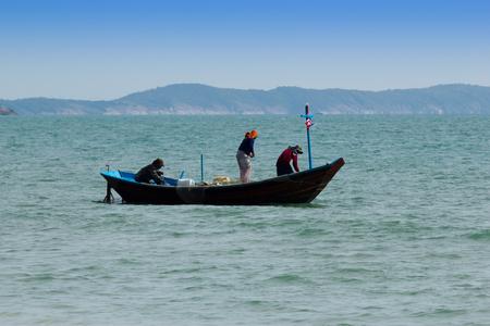 Fishermen pulling net in Sea Stock Photo