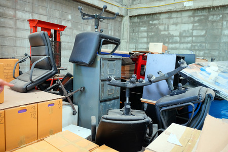 Broken office chairs and wooden cabinet in the store room Stockfoto