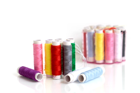 Small multicolor sewing threads row for quick repair clothes with blur background