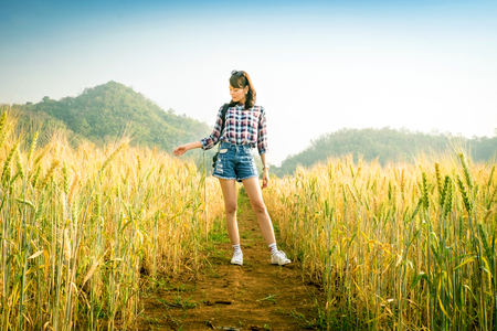 Beautiful asian woman pose in gold barley wheat field at sunset time