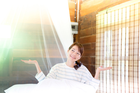 Beautiful young smiling asian woman sitting on bed and Raise arm in the morning at bedroom.