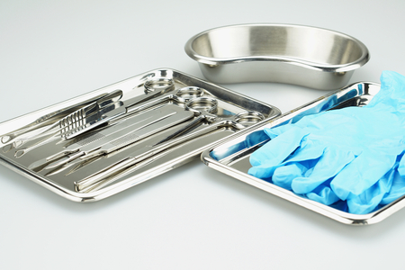 Medical instruments and blue gloves in a stainless steel tray on white table.