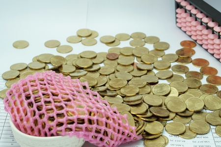 workload: Gold coins in the cup overflow distributed on financial document with a pink abacus.