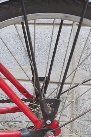 rear wheel: The rear wheel of the red bicycle has silver spokes parked on the side wall.