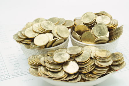 workload: Pile of gold coins in ceramic as ship placed on financial documents.