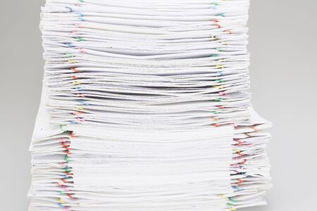 Pile of overload white paper and reports on white table. Stock Photo