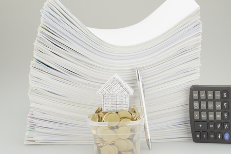 bucket of money: House on a pile of money in bucket with pen and calculator have documents as background. Stock Photo