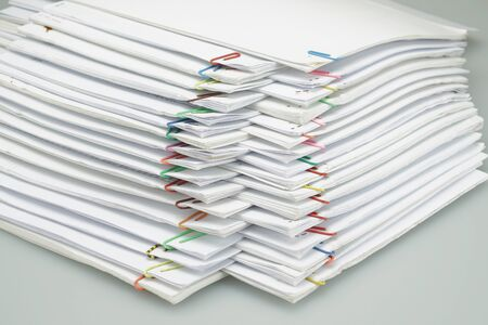 Colorful paper clip with pile of overload white paperwork and reports arranged on white table. Stockfoto