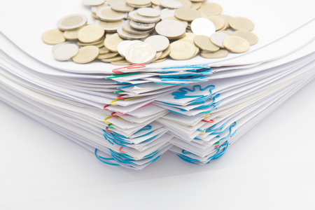 Step pile of paperwork with colorful paperclip have stack of gold coins on a white background.
