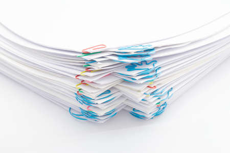 Step pile of paperwork with colorful paperclip on a white background.