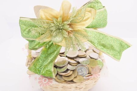 Stack of gold coins in basket with green ribbon on a white background.