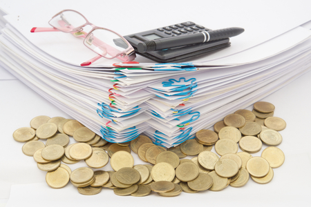 Stack of gold coins with pile of paperwork have pen with spectacles and calculator on a white background.