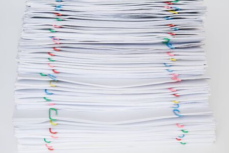 Colorful paper clip with pile of overload paper and reports place on white table.