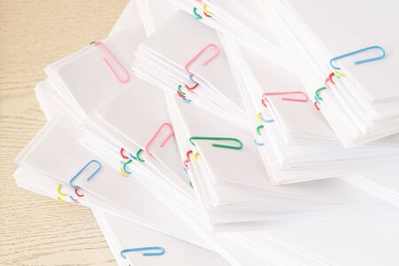 Colorful paper clip with stack of overload paperwork and reports place on wooden table.