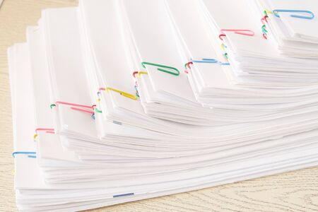 Colorful paper clip with step stack of overload paper and reports place on wooden table.