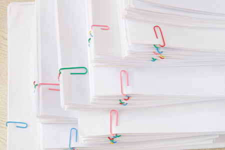 Stack of overload document and reports with colorful paper clip place on wooden table.
