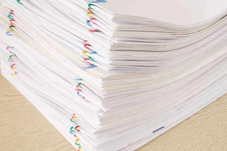 Colorful paper clip with pile of overload paperwork and reports place on wooden table. Stockfoto