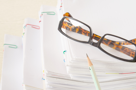 Pencil and spectacles put on stack of overload paper and reports place on wooden table.