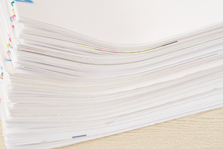 Stack of overload paperwork and reports place on wooden table. Stockfoto