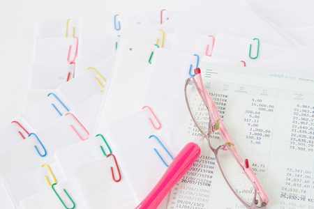 Pink spectacles and pen with book bank put on stack of overload paper and reports place on white table. Stockfoto