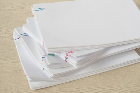 Colorful paper clip with pile of overload document and reports place on wooden table. Stockfoto