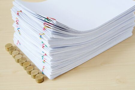 Pile of overload paper and reports with colorful paper clip and pile of gold coins place on wooden table. Stockfoto