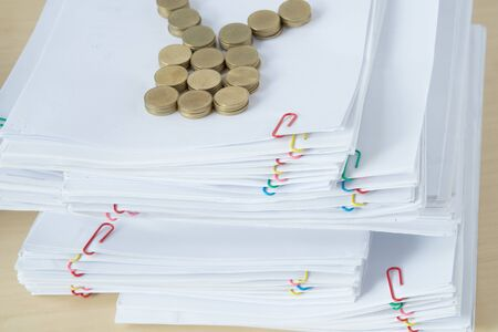 Pile of overload document and reports with colorful paper clip have blur pile of gold coins place on wooden table.